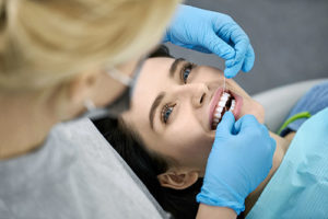 woman being flossed by a dentist, dental implants services