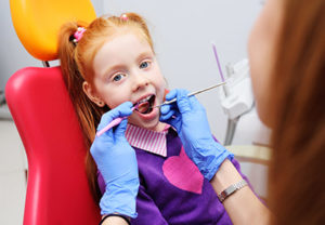 girl with open mouth being examined by a dentist, pediatric dentistry pasadena tx